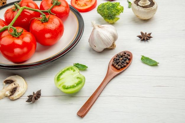 Onderaanzicht rode tomaten op witte plaat knoflook paddestoel anijs zwarte pepers in houten lepel op grijze tafel