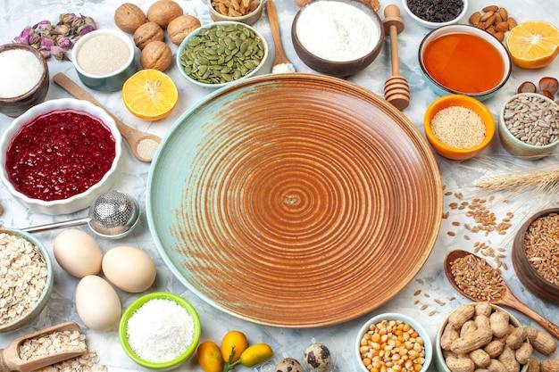 Onderaanzicht ronde bord kommen met maïszaden kokospoeder pompoenpitten zonnebloempitten tarwekorrels jam walnoten eieren cumcuats