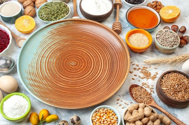 Onderaanzicht ronde bord kommen met maïszaden pinda's tarwekorrels honing cumcuats walnoten honing stick