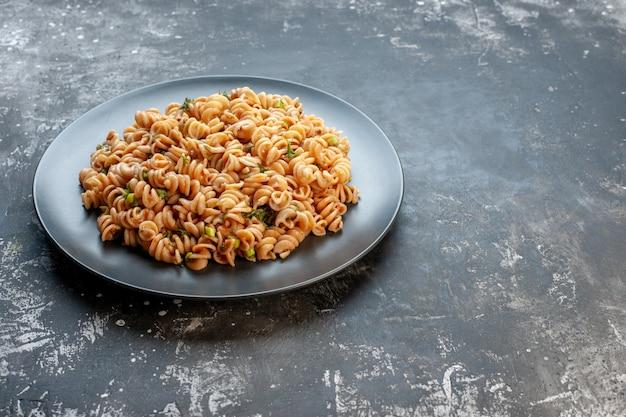 Onderaanzicht rotini pasta op ronde plaat op donkere oppervlakte kopieerplaats