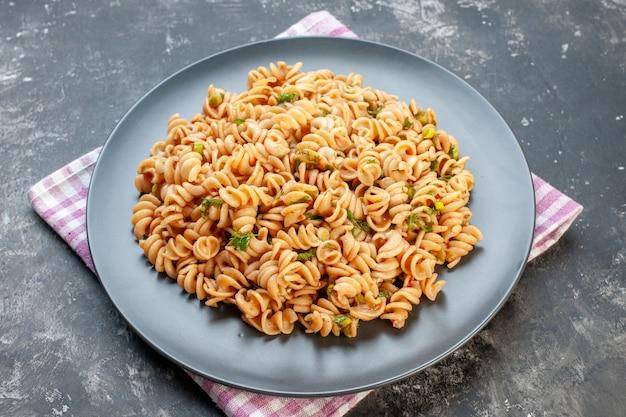Onderaanzicht rotini pasta op ronde plaat op roze wit geruit servet op grijze tafel