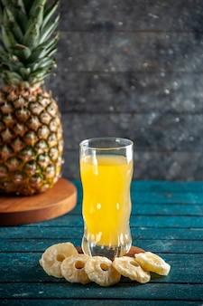 Onderaanzicht sap glas droge ananas plakjes verse ananas op houten bord op grijze achtergrond