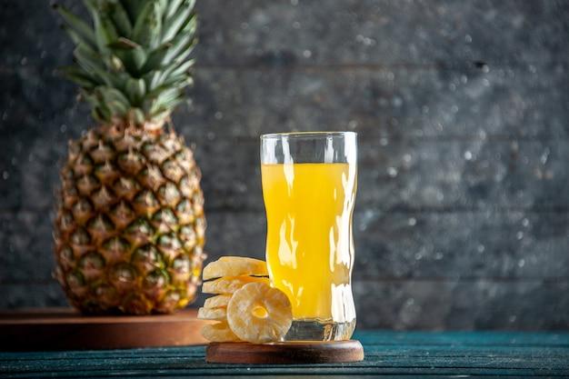 Onderaanzicht sap glas droge ananas plakjes verse ananas op houten planken op grijze achtergrond