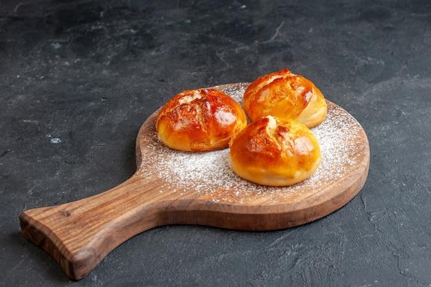 Onderaanzicht smakelijke dinerbroodjes op een houten bord op zwarte muur