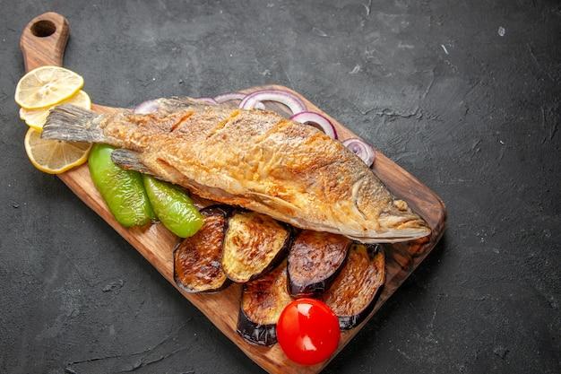 Onderaanzicht smakelijke vis bakken gebakken aubergines ui op houten serveerplank op donkere achtergrond