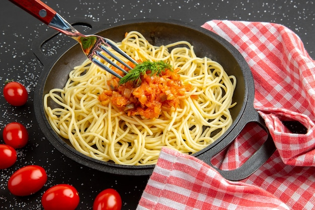 Onderaanzicht spaghetti met saus in koekenpan vork cherrytomaatjes op zwarte tafel