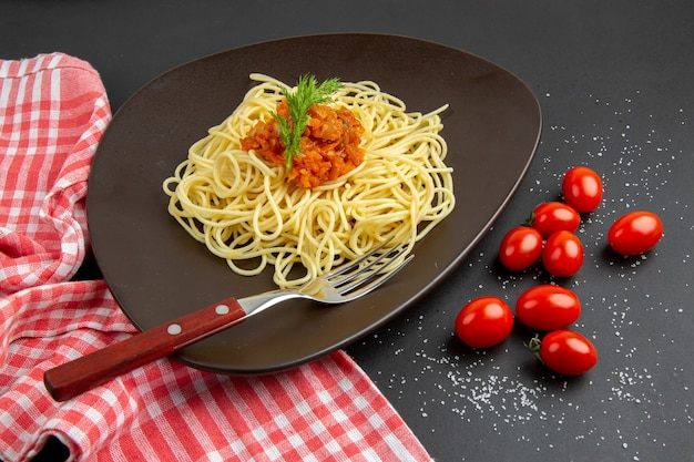 Onderaanzicht spaghetti met sausvork op plaat cherrytomaatjes rood wit geruite keukenhanddoek op zwarte tafel