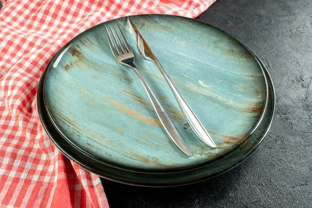 Onderaanzicht stalen vork en diner mes op ronde schotel rood en wit geruit tafelkleed op zwarte tafel