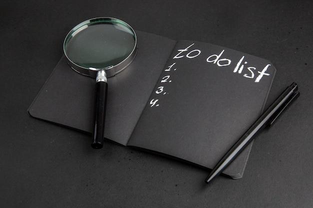 Onderaanzicht takenlijst geschreven op zwarte notitieblok lupa pen op zwarte tafel