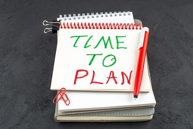 Onderaanzicht tijd om te plannen geschreven op spiraal notebook rode pen edelsteen clips bindmiddel clip op donkere achtergrond