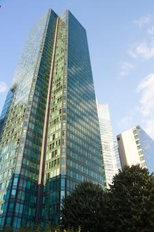 Onderaanzicht van de glazen wolkenkrabbers van het zakelijke district van la defense van parijs tegen een blauwe bewolkte hemel