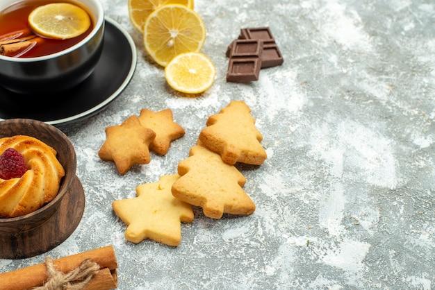 Onderaanzicht van dichtbij een kopje thee schijfjes citroen kaneelstokjes koekjes chocolade op grijs oppervlak vrije ruimte