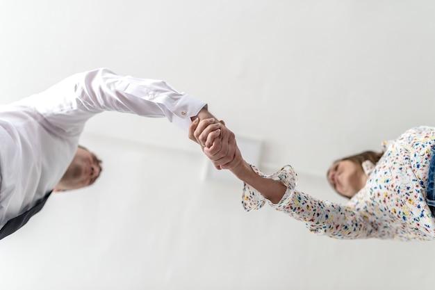 Onderaanzicht van een handdruk van een zakenman en vrouw conceptuele van een zakelijke overeenkomst of partnerschap met kopie ruimte.