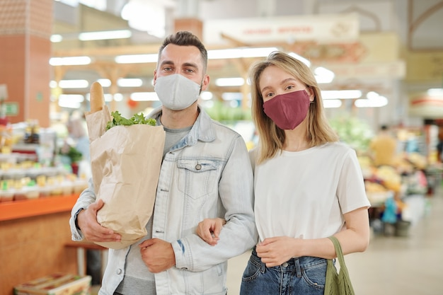 Onderaanzicht van een jong stel met gezichtsmaskers dat samen over de boerenmarkt loopt tijdens het coronavirus en voedsel koopt