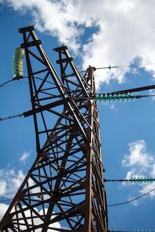 Onderaanzicht van een metalen paal van een hoogspanningslijn met een veelvoud van elektrische draden