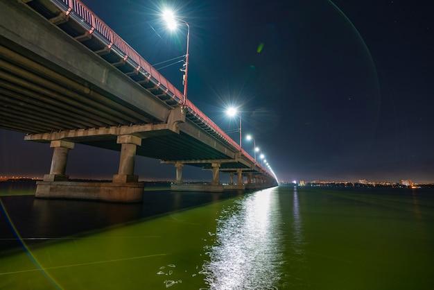 Onderaanzicht van een mooie heldere lange brug met koude lichten en snelle auto's over de grote mooie rivier de dnjepr in dnepropetrovsk in het prachtige oekraïne
