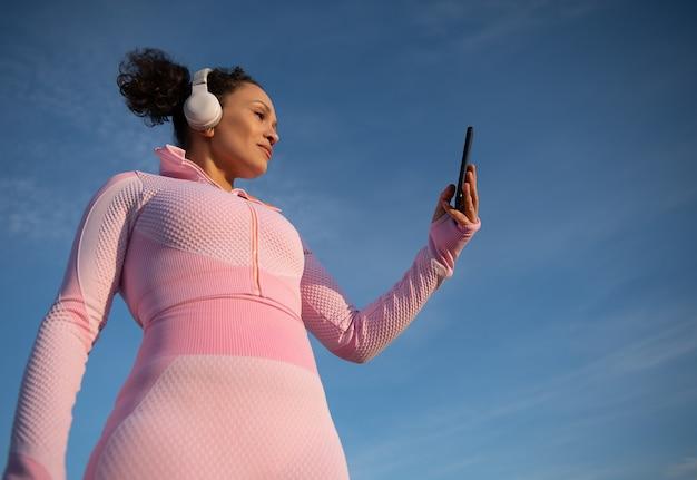 Onderaanzicht van een mooie sportvrouw in roze sportkleding met koptelefoon en een mobiele telefoon in haar hand tegen het oppervlak van een mooie heldere blauwe lucht