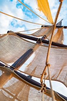 Onderaanzicht van een scheepsmast met beige zeilen
