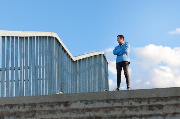 Onderaanzicht van een sportieve actieve man in een blauwe jas, staat op de brug en kijkt weg, genietend van de schoonheid van de natuur, vrijheid.