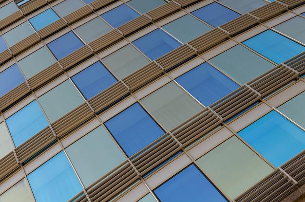 Onderaanzicht van glazen wand van blauwe en gouden kleuren met ramen