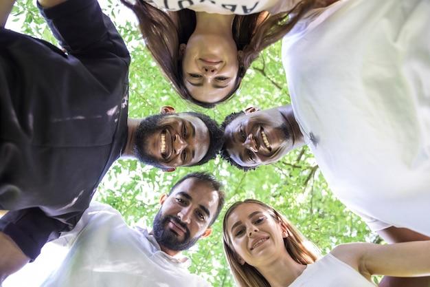 Onderaanzicht van groep van uiteenlopende vrienden poseren