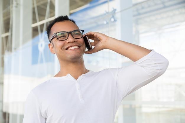 Onderaanzicht van lachende man praten over telefoon op kantoor gebouw