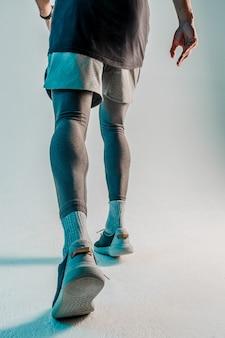 Onderaanzicht van loper. sportman draagt sportuniform. geïsoleerd op turkooizen achtergrond. studio shoot