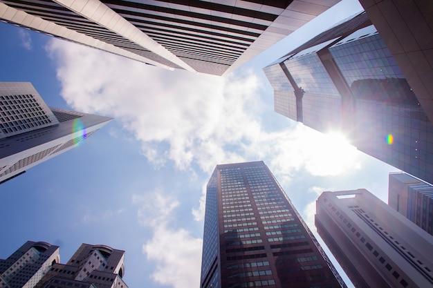 Onderaanzicht van moderne wolkenkrabbers / kantoorgebouwen in het zakelijke district van de steden van singapore tegen de blauwe hemel. economie, financiën, bedrijfsactiviteit concept. kopieer ruimte voor inhoud.