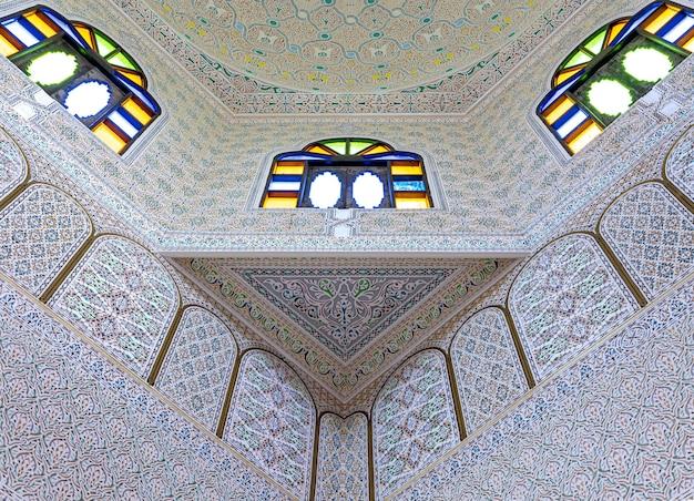 Onderaanzicht van plafond met glas in lood ramen en veel ornamenten en details in traditionele oosterse stijl.