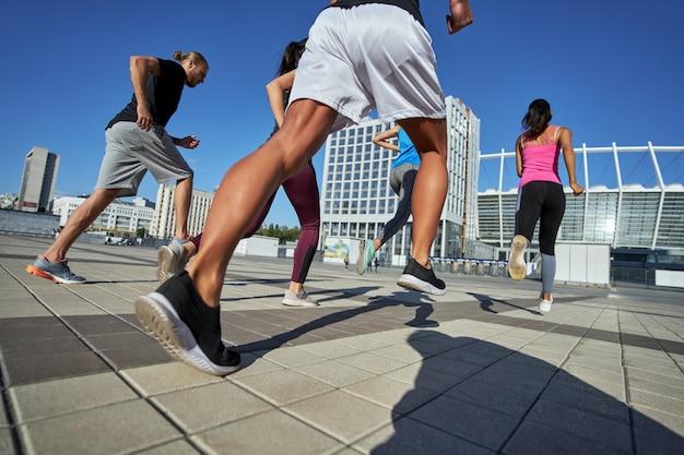 Onderaanzicht van sporters die over een verhard terrein rennen