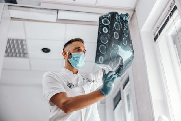 Onderaanzicht van toegewijde arts die röntgenfoto van de hersenen van de patiënt vasthoudt en ernaar kijkt.