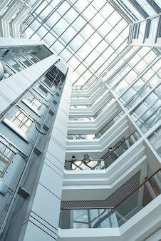 Onderaanzicht van verschillende zakenmensen die werkpunten bespreken terwijl ze op een van de balkons in een groot kantoorcentrum staan