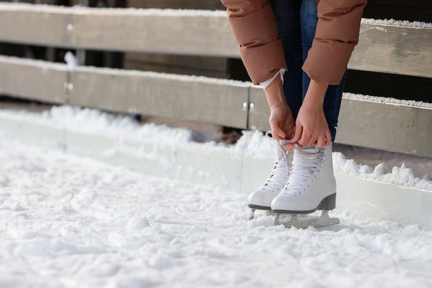 Onderaanzicht van vrouwelijke veters strikken / witte schaatsen dragen op ijsbaan in de winterdag. weekendactiviteiten buiten bij koud weer