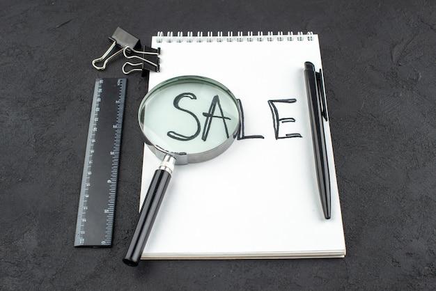 Onderaanzicht verkoop geschreven op notitieblok pen liniaal bindmiddel clips lupa op donkere achtergrond