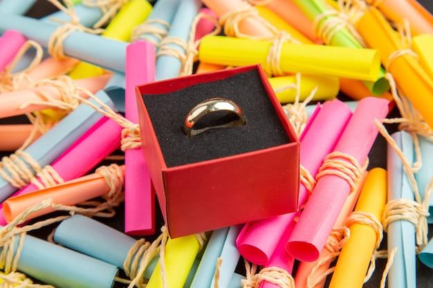 Onderaanzicht verlovingsring in doos op scroll wenspapieren