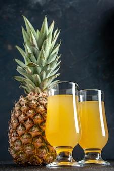 Onderaanzicht vers ananas ananassap in glazen op donkere achtergrond