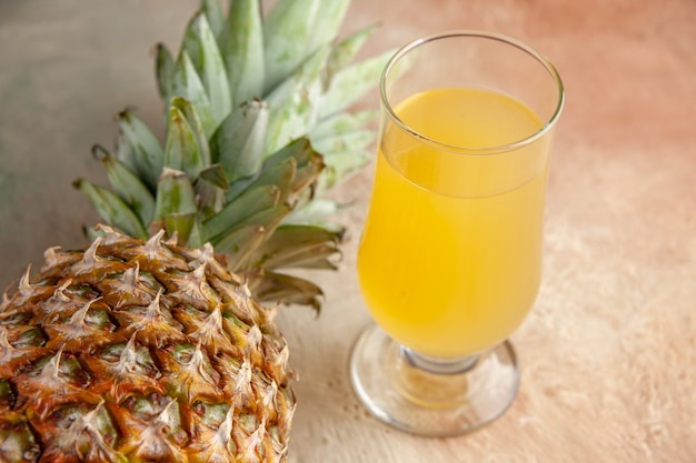 Onderaanzicht vers ananassap in glas op beige achtergrond