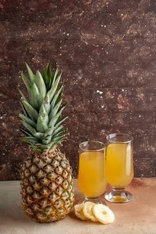 Onderaanzicht vers ananassap in glazen droge ananasschijfjes op bruine achtergrondkopieerplaats