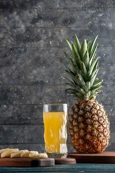 Onderaanzicht vers sap in glas op een houten bord verse ananas op een houten bord op een grijze achtergrond