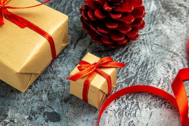 Onderaanzicht verschillende maten cadeautjes gebonden met rood lint dennenappel op donker