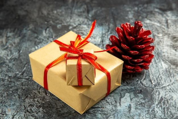 Onderaanzicht verschillende maten cadeautjes gebonden met rood lint gekleurde dennenappel op donkere geïsoleerde achtergrond