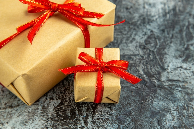 Onderaanzicht verschillende maten cadeautjes vastgebonden met rood lint op donker