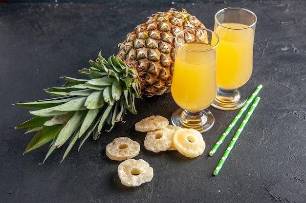 Onderaanzicht verse ananas met droge ananasschijfjes ananassap in glazen op donkere achtergrond