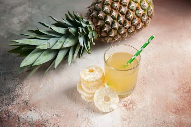 Onderaanzicht verse ananas tot vaststelling van sap glazen pipet droge ananas ringen op beige achtergrond