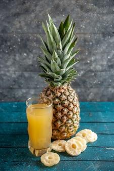 Onderaanzicht verse ananassap glas gedroogde ananas ringen op grijze achtergrond