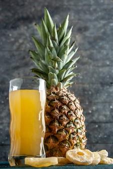 Onderaanzicht verse ananassap glas gedroogde ananas ringen op grijze houten achtergrond