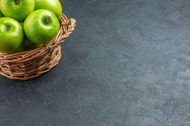 Onderaanzicht verse appels in rieten mand op donkere ondergrond met vrije ruimte