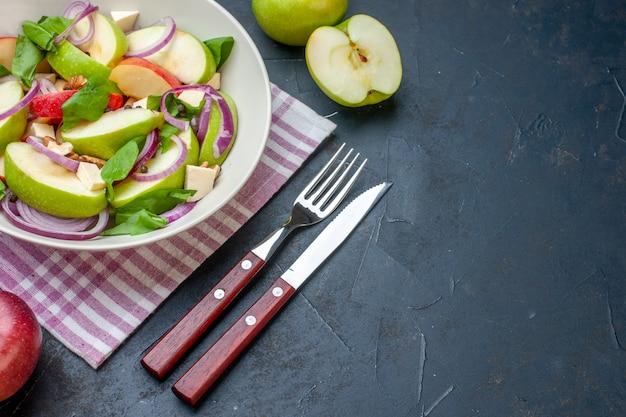 Onderaanzicht verse appelsalade in witte kom appels paars en wit geruit tafelkleed vork en mes op donkere tafel vrije ruimte