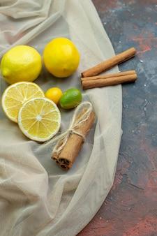 Onderaanzicht verse citroenen gesneden citroenen cumcuats kaneelstokjes op tule op donkerrode grond