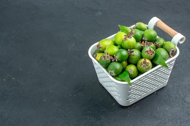 Onderaanzicht verse feijoa's op plastic mand op donkere ondergrond met kopieerruimte Gratis Foto
